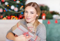 Receiving Christmas gifts. Pretty girl with pleasure receiving Christmas gifts, spending happy time at home in winter holidays stock photos