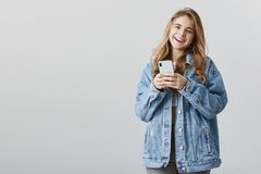 Receiving compliments about new device. Attractive pleased friendly girlfriend in trendy denim jacket, holding. Smartphone and smiling cheerfully, expressing royalty free stock photos