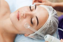Receiving electric darsonval facial massage procedure at beauty salon. royalty free stock photography