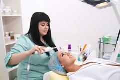 Receiving electric darsonval facial massage procedure. Stock Photo