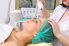 Receiving electric darsonval facial massage procedure. Royalty Free Stock Photography