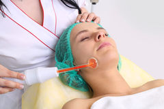 Receiving electric darsonval facial massage procedure. Royalty Free Stock Photo