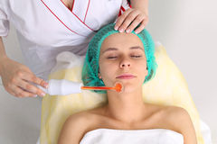 Receiving electric darsonval facial massage procedure. Stock Photography