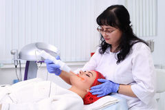 Receiving electric darsonval facial massage procedure. Royalty Free Stock Image