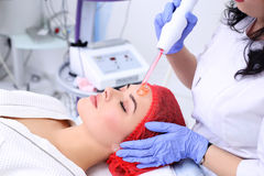 Receiving electric darsonval facial massage procedure. Stock Images