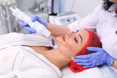 Receiving electric darsonval facial massage procedure. Royalty Free Stock Photos