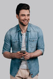 Receiving funny messages. Handsome smiling young man in blue jeans shirt holding smart phone and looking away while standing against grey background Royalty Free Stock Image