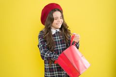 Receiving gift. Adorable small child taking up surprise gift on yellow background. Cute little girl holding shopping bag. With present. Gift shop. Gift delivery royalty free stock photo