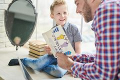 Receiving Gifts for Fathers Day. Lovely moments of fatherhood: joyful bearded men reading handmade greeting card given by his little son for Fathers Day while Stock Photo