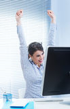 Receiving good news. Young joyful woman at desk with fists raised receiving good news Stock Images