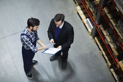 Receiving goods. Dispatcher of warehouse signing document before receiving goods Royalty Free Stock Image