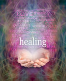 Receiving healing. Female cupped hands with the word 'healing' floating above surrounded by a word cloud of healing related words on a swirling misty energy stock photography