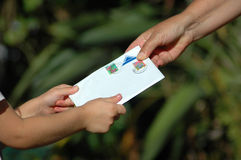 Receiving a letter. A little white hand of a caucasian girl toddler receiving a letter from her grandmother in the garden during sunset Royalty Free Stock Image