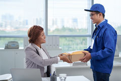 Receiving mail. Business women receiving package from delivery man Stock Photos