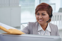 REceiving mail at work. Pretty smiling call center operator receiving package Stock Images