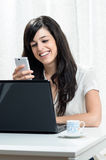 Receiving message. Smiling brunette woman reading a message in her white cellphone while she uses her laptop Stock Images