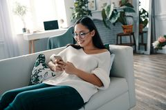 Receiving messages from friend. Beautiful young woman using smart phone and smiling while spending time at home stock photos