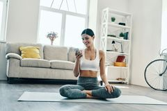 Receiving nice messages. Beautiful young woman in sports clothing using smart phone and smiling while practicing yoga at home stock photo