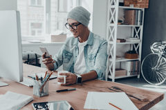 Receiving nice messages. Handsome young man holding a cup and looking at smart phone with smile while sitting at his working place in creative office Stock Photos