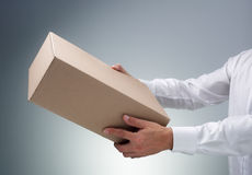 Receiving a package. Businessman receiving or giving a cardboard box package or parcel Royalty Free Stock Photography