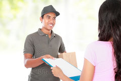 Receiving a package at home. Woman receiving a package at home from a delivery guy Royalty Free Stock Photos