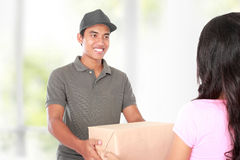 Receiving a package at home. Woman receiving a package at home from a delivery guy Stock Photo