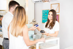 Receiving payment with a credit card. Beautiful young women working at a jewelry store getting paid with a credit card and smiling Royalty Free Stock Photos