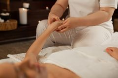Experienced massage master pressing on dots on the hand of her client. Receiving relaxing massage . Experienced massage master pressing on dots on the hand of stock images