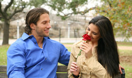 Receiving Rose. Young girl smelling rose given by her boyfriend royalty free stock photo
