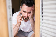 Receiving some bad news on the phone. Worried man talking on the phone in bedroom's window royalty free stock image