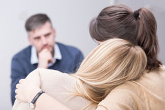 Receiving understanding and support from her therapy group. Close-up of two women, hugging in a supportive pose and a men in a blurry background Royalty Free Stock Photos