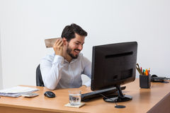 Receiving voice message during work hours. Listening to a voice message at office, laughing and relaxed Royalty Free Stock Images