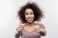 Dark-eyed curly woman feeling happy after receiving work of her dreams stock photos