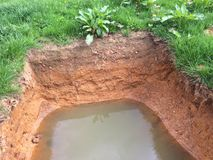 Soil strata and hole in the ground. A recent excavation on farmland in Devon showing the soil strata and poor drainage royalty free stock photography