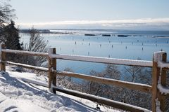 A snow covered fence provides foreground elements agains blue waters. A recent snowfall has coated a wood fence which contrasts with bright blue waters of a royalty free stock photos