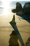Recente middagzon die een strand met rotsen en zand raken Stock Foto