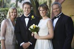 Recentemente coppia sposata che sta con i genitori fotografia stock