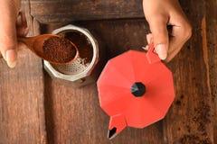 Recentemente feijões de café em feijões da chaleira vermelha e de café à terra na bacia Imagem de Stock Royalty Free