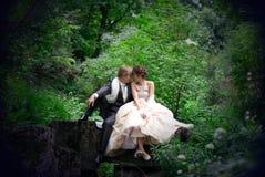 Recentemente o casal que senta-se na rocha no th Imagens de Stock Royalty Free