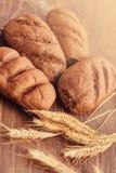 Recentemente produtos da padaria e spikelets deliciosos do trigo no fundo de madeira fotos de stock