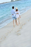 Recently married couple making romantic walk on the beach Stock Photo