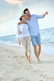 Recently married couple walking on the beach at sunset Stock Image