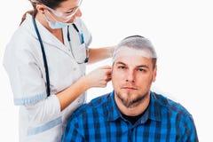 Recently operated man. Nurse applying a bandage to a men who had a head trauma stock photo