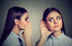 Recentste Geruchten Vrouw die in het oor aan zich fluisteren stock fotografie