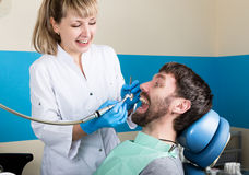 A recepção estava no dentista que fêmea Doctor examina a cavidade oral na deterioração de dente Proteção da cárie o doutor põe Imagens de Stock Royalty Free