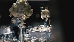 Recepción, celebrando en el restaurante Tablas blancas de la ronda grande adornadas con las flores blancas y la comida deliciosa metrajes