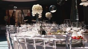 Recepción, celebrando en el restaurante Tablas blancas de la ronda grande adornadas con las flores blancas y la comida deliciosa almacen de video