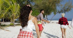Recepción de la chica joven usted a correr con la gente feliz en la playa, hombres de la raza de la mezcla y turistas del grupo d almacen de metraje de vídeo