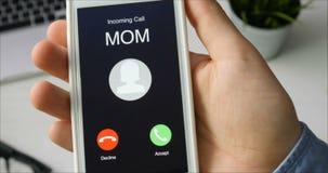 Recepción de llamada de teléfono de mamá y el aceptar Concepto de la comunicación móvil El sentarse en el escritorio