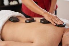 Recepción de masaje con las piedras calientes Foto de archivo libre de regalías